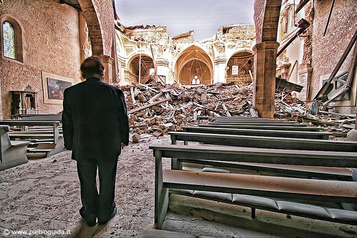 Una foto simbolo del terremoto dell'Aquila, il parroco della basilica di Collemaggio guarda la devastazione