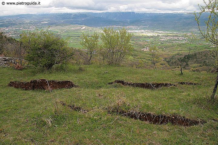 Spaccature sul terreno causate dalla faglia di Bagno e sullo sfondo una veduta dell'Aquila